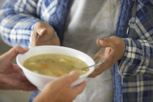 Volunteer giving bowl of soup to survivor